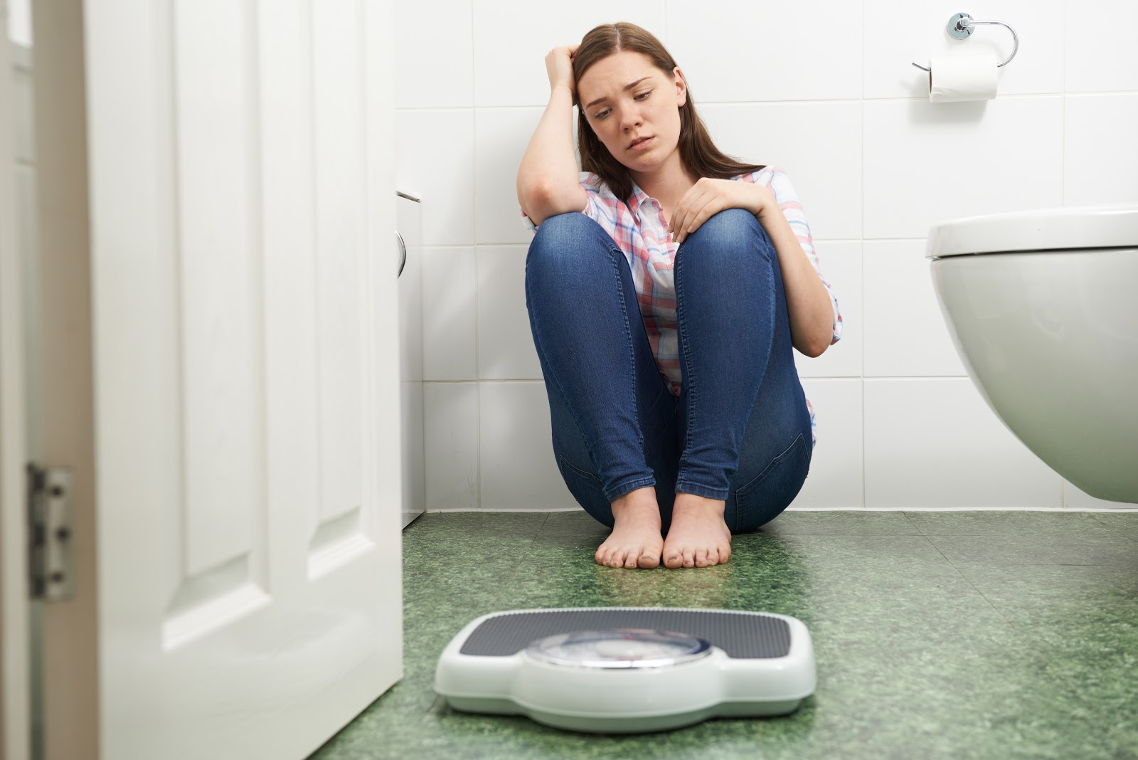 sad woman sitting on bathroom floor behind scale