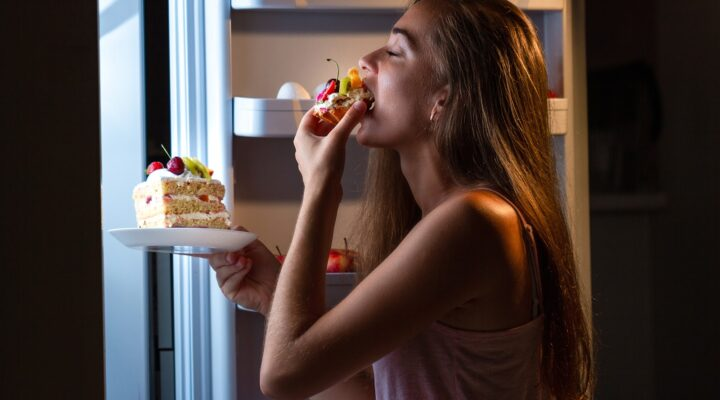 girl standing in front of an open refrigerator eating cake with her hand